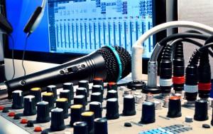 Mikrofon auf Mischpult mit Laptop und mikrigen Kopfhörern